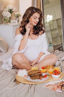 朝食を食べてベッドで幸せな妊娠中の女性