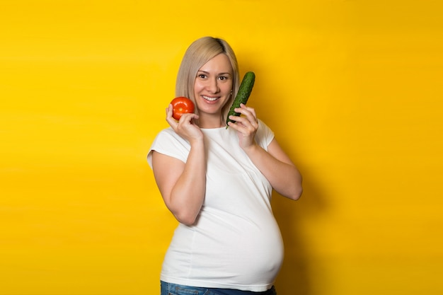 Happy pregnant woman chooses between pills and vegetables on a yellow wall. nutrition and diet during pregnancy