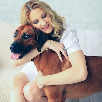Happy pregnant woman and a dog sitting on a couch cuddling cute