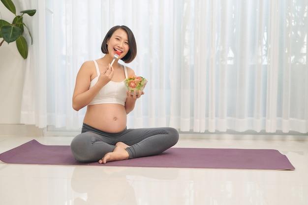Счастливая беременная женщина ест овощной салат