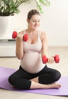 Счастливая беременная женщина, тренирующаяся с красными весами на фитнес-коврике дома