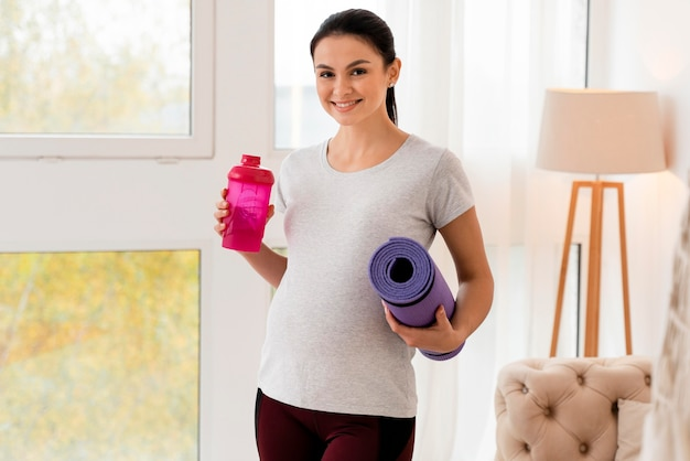 フィットネスマットと水のボトルを保持している幸せな妊婦