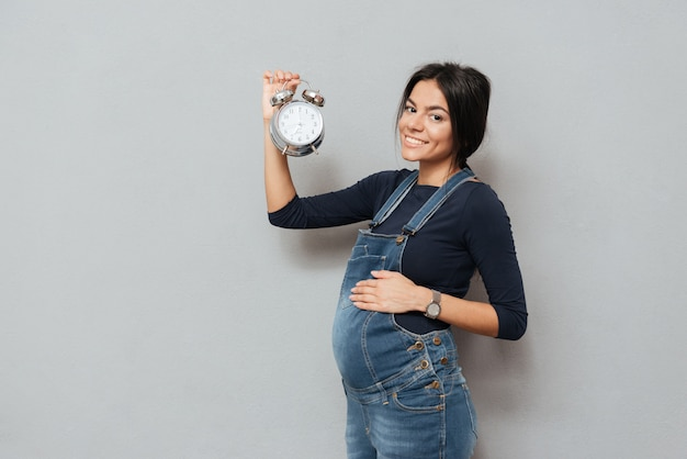 Happy pregnant woman holding watch over grey wall
