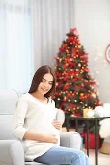 크리스마스 장식 방에 행복 한 임신 여자