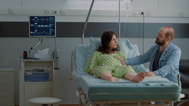 幸せな妊婦は、赤ちゃんのバンプに手をつないでいる子供の父親と一緒に病棟のベッドに横たわっています。出産と親のライフスタイルを待って期待して座っている白人カップル