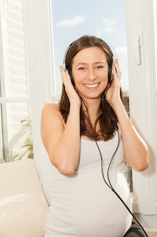 Happy pregnant woman listening to music