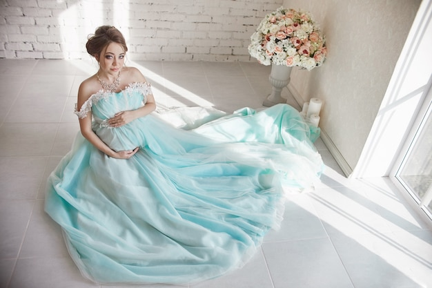 Happy pregnant woman in long evening dress touching belly