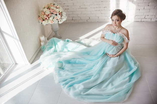 Happy pregnant woman in long evening dress
