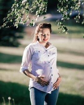 彼女の腹を見て幸せな妊娠中の女性