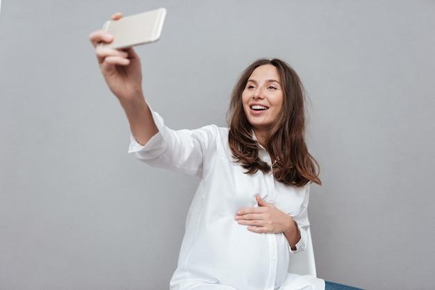 Счастливая беременная женщина делает селфи в студии, изолированной сером фоне