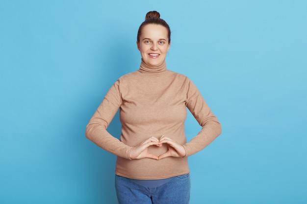 행복 한 임신 여자는 그녀의 배꼽 앞에서 심장 제스처를 만들고, 캐주얼 복장을 입고, 머리 롤빵, 파란색 벽에 고립 된 서 어머니를 기대.
