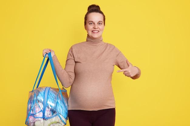 幸せな妊婦は、彼女の胃を指して、産科病院に行く準備ができている妊婦を笑顔で、幸せそうに見え、カジュアルな服を着て、黄色い壁の上に孤立してポーズをとっています。