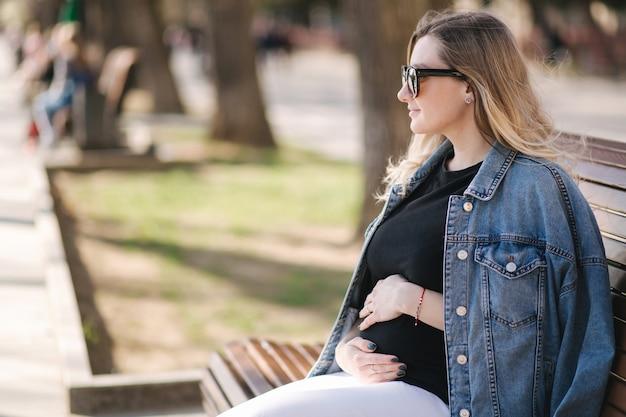 幸せな妊娠中の女性が公園のベンチに座っている腹に手を置きます