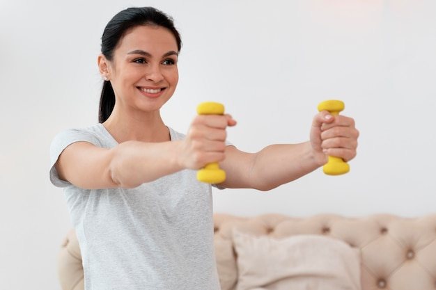 Happy pregnant woman using yellow weights