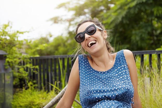 Счастливая беременная женщина в солнечных очках и синем платье, расслабляющаяся на открытом воздухе на фоне зеленой природы