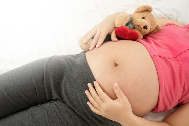 임신 배꼽에 아기와 함께 행복 한 임신 여자. 모성 산전 관리 및 여성 임신.