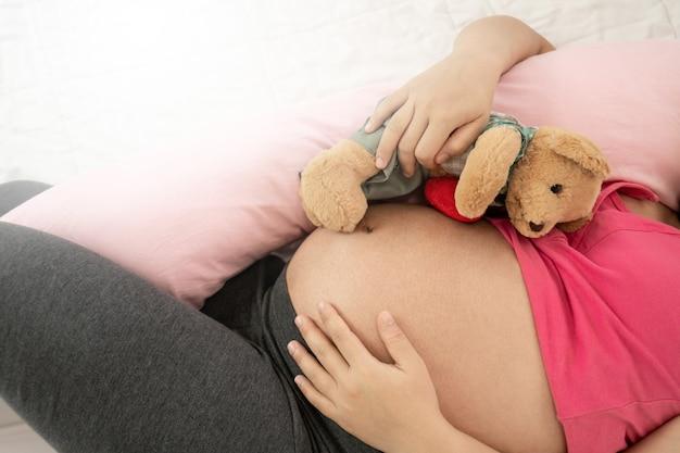 妊娠中の腹に赤ちゃんと幸せな妊娠中の女性。
