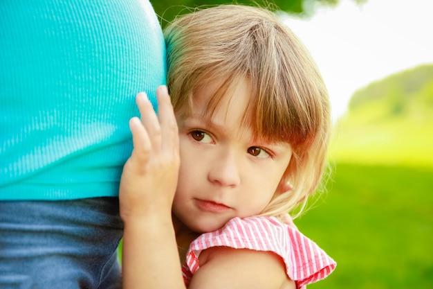 公園で自然に赤ちゃんと幸せな妊娠中の女性