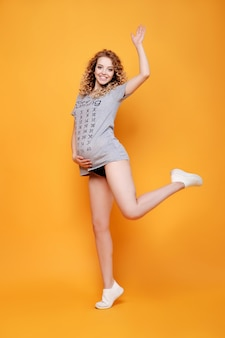 Happy pregnant young beautiful fashion blonde model woman jump motion in studio on yellow orange smilles