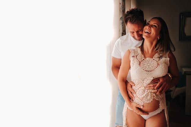흰색 배경 옆에 행복 한 임신 젊은 부부