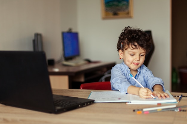 A happy preschool child is trained online on a laptop and does homework in a notebook. a cute, joyful curly boy looks at the monitor screen in a room of his house.