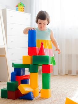 행복한 미취학 아동은 장난감 블록을 가지고 놀아요.