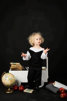 Happy preschool girl near the cart with a books, globe and clock on a black background