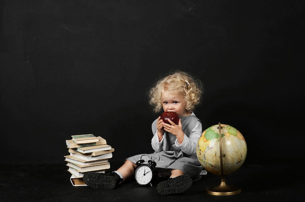 Happy preschool girl with a books, globe and clock on a black background
