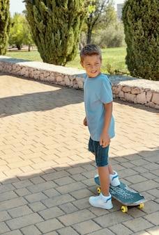 Счастливый дошкольник в футболке учится кататься на скейтборде в парке. макет рубашки
