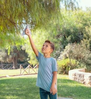 Счастливый мальчик дошкольника играет с бумажным самолетиком в парке