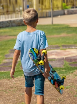 Happy preschooler boy in t-shirt keep a skateboard in hands outdoors. cute child doing sports and having fun in park. active hobbies, healthy lifestyle concept. t-shirt mockup, back view