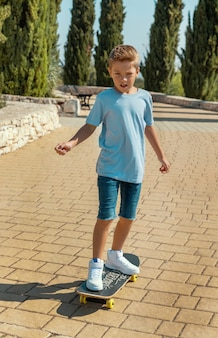 Happy preschooler boy in t-shirt learning to ride a skateboard in a park. shirt mockup