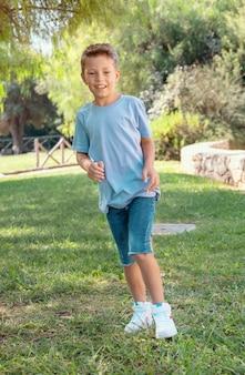 Счастливый мальчик ребенк дошкольника работает открытый в парке в солнечный день. милый ребенок в рубашке и джинсовых шортах занимается спортом и развлекается. активные увлечения, концепция здорового образа жизни. макет футболки