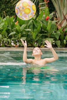 Happy preteen boy playing with inflatable ball in swimming pool of spa hotel
