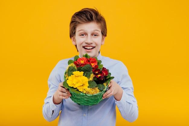 Счастливый малолетний мальчик с корзиной цветов в руке, в синей рубашке, изолированной на желтой стене