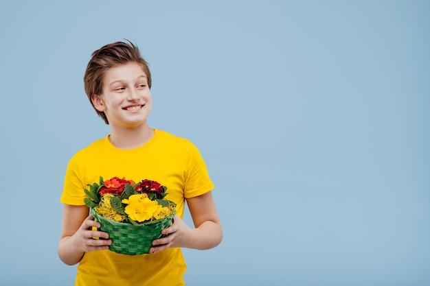 Счастливый малолетний мальчик с корзиной цветов в руке, в желтой футболке, изолированной на синей стене, копией пространства, отвести взгляд