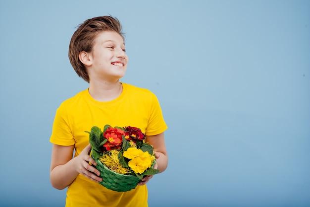 Счастливый малолетний мальчик с корзиной цветов в руке, в желтой футболке, изолированной на синей стене, копией пространства, видом в профиль