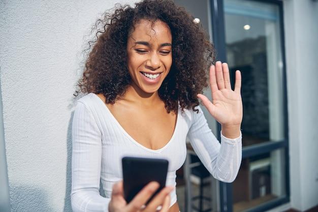 電話で話し、誰かを振っている間幸せそうに見える幸せなかなりアフリカ系アメリカ人の女性