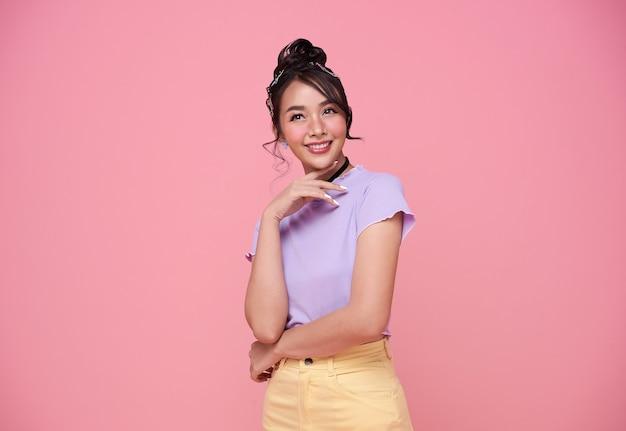 ピンクの背景に分離された幸せなかわいいアジアの10代の少女。