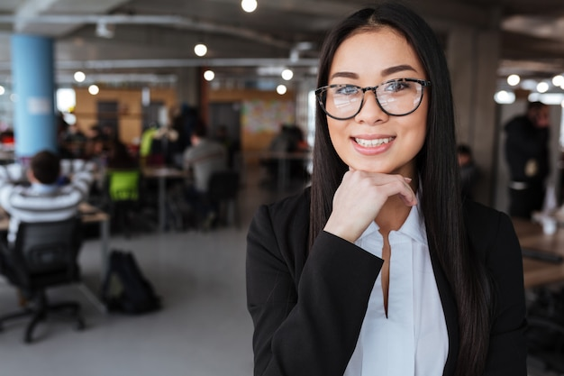 Happy pretty asian young businesswoman standing in office