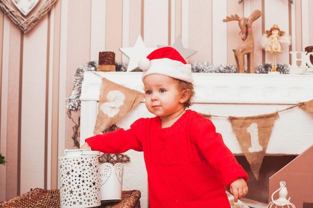 クリスマスプレゼントとコスチュームサンタクロースに身を包んだ幸せなかわいい赤ちゃん