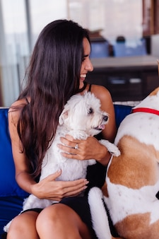 Happy pretty beautiful woman relaxing at home on sofa with pet dogs