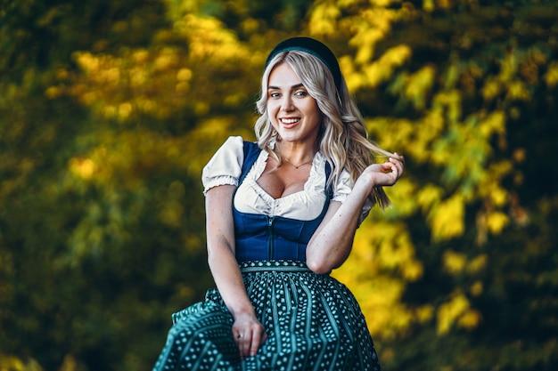 Счастливая милая белокурая девушка в платье dirndl, традиционном фестивале пива, сидя outdoors с blured красочными деревьями позади