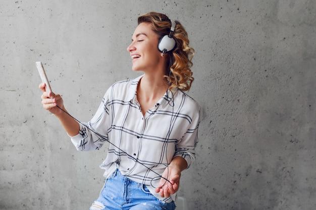灰色の都市壁の背景に椅子に座って、イヤホンで音楽を楽しんで幸せなかなり金髪流行に敏感な女性。