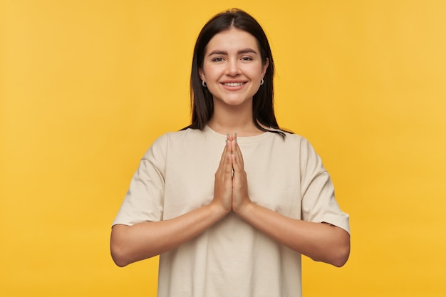 Felice bella giovane donna bruna in maglietta bianca tiene le mani in posizione di preghiera sul muro giallo