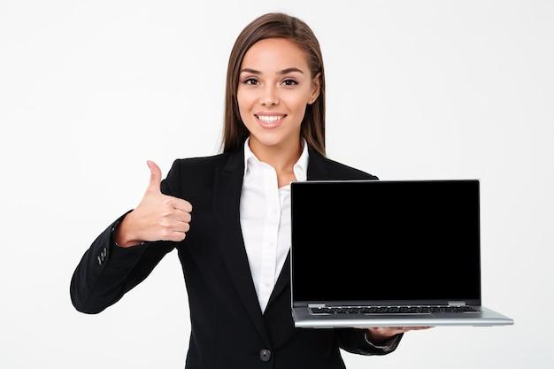 Счастливая милая коммерсантка показывая дисплей компьтер-книжки с большими пальцами руки вверх
