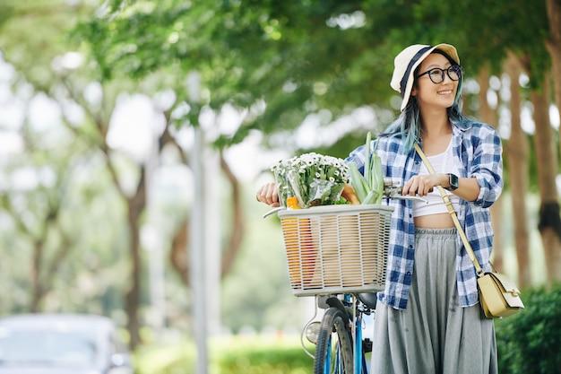 Счастливая симпатичная китайская девочка-подросток наслаждается прогулкой в парке со своим велосипедом и смотрит вокруг