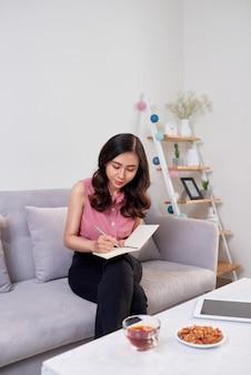 Счастливый довольно милая женщина писать в тетради, сидя с ноутбуком в гостиной