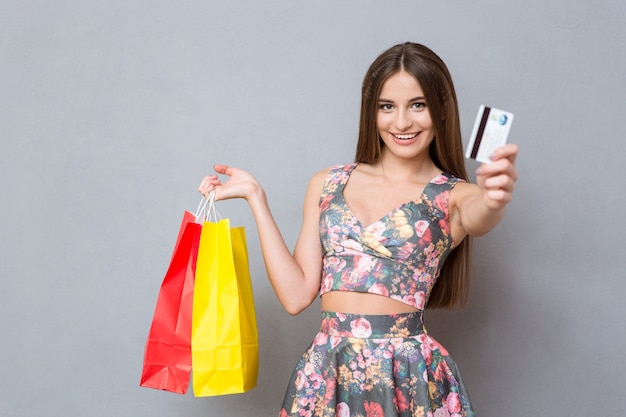 クレジットカードを見せて、カラフルなバッグを持って、笑顔で長い髪の幸せなかなり興奮した女性の買い物客