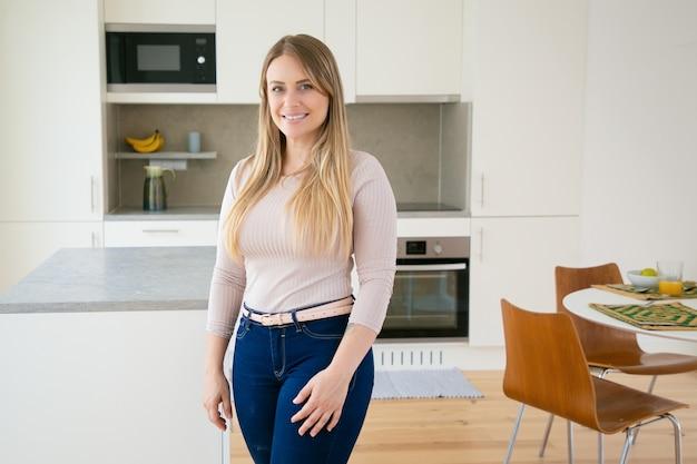 幸せなかなり公正な髪の若い女性がキッチンでポーズ
